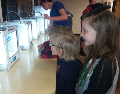 The Kakavas family watches an Ultimaker machine create a  3-D model.