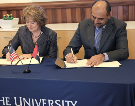 UA President Ann Weaver Hart and alumnus Abdullah Al Hashimi of Emirates Group Security sign one of two agreements at the Gulf Cooperation Council alumni reunion.