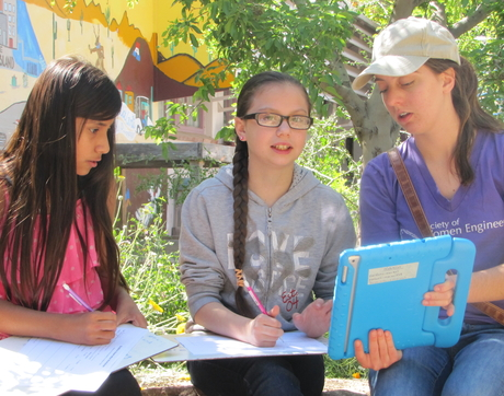 A UA intern working with students to collect biodiversity observations using iNaturalist.