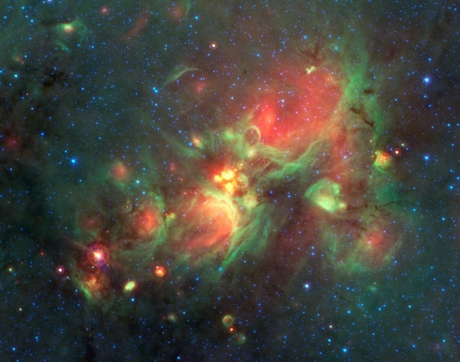 The yellow balls seen at the center of this image are a phase of massive star formation that comes before the massive stars have cleared cavities in the clouds of gas around them (shown in green) but after the cold, collapsing gas stage that Jenny Calahan and Yancy Shirley searched for in their survey. (Courtesy of NASA/JPL-Caltech)