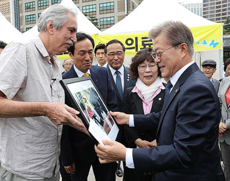 Professor Kim Newton hands South Korean President Moon Jae-in a 1987 photo. Woo Sang-ho (next to Newton) was one of the students in the photo. (Newsis image)
