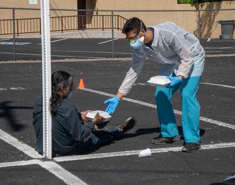 Medical student Christian Bergman distributes breakfast to a homeless man. (Photo by Rick Kopstein/Biocommunications)