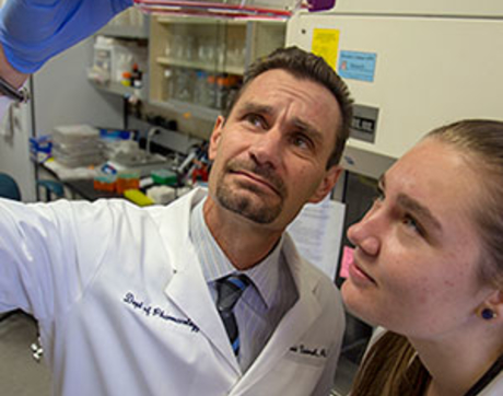 Todd Vanderah and undergraduate researcher Angela Smith work in the lab.