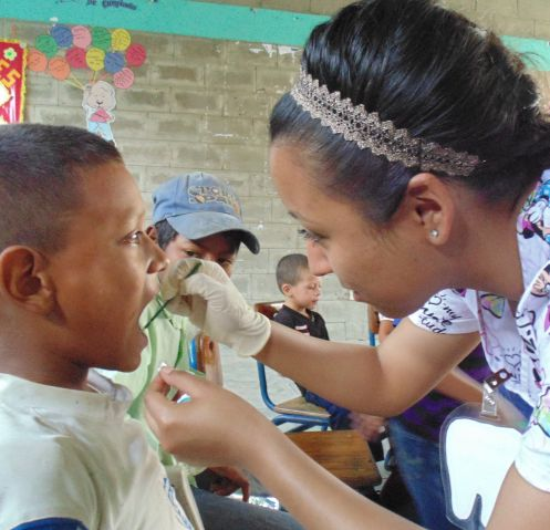 UA student Nicole Guillen gives a fluoride treatment to a child in Honduras. Guillen helped provide an educational workshop on dental hygiene as part of Global Dental Brigades. (Photo courtesy of Niam Ismail/UA Global Medical Brigades)