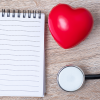 A note pad, stethoscope, and heart-shaped stress ball.