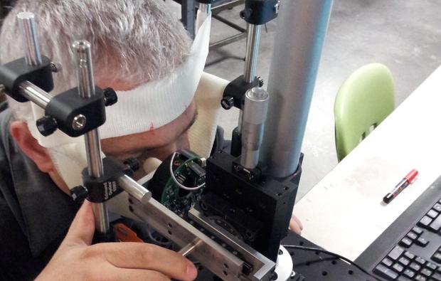UA associate professor and inventor Eniko Enikov demonstrates use of the non-invasive eye tonometer. (Photo: Eniko Enikov)