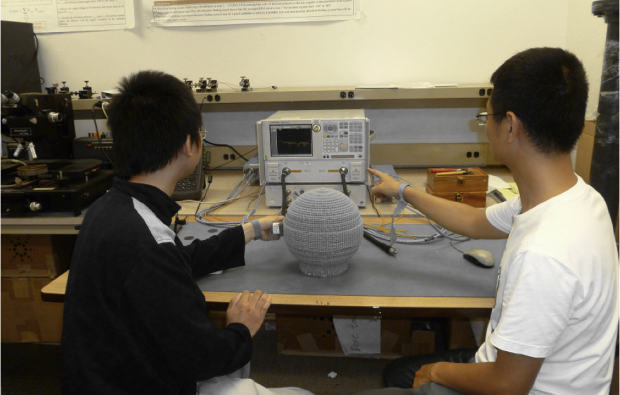 Students in Hao Xin's lab perform measurements on a 3-D printed prototype of a Lüneburg lens. (Image: Hao Xin)
