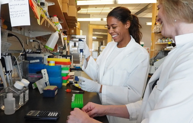 Student Bre Eder (left) and associate professor Felicia Goodrum, working side by side in Goodrum's lab.