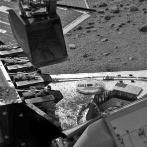 This image taken by the Surface Stereo Imager on NASA's Phoenix Mars Lander shows the lander's Robotic Arm scoop positioned over the Wet Chemistry Lab delivery funnel on Sol 29, the 29th Martian day after landing, or June 24 2008. The soil will be delivered to the instrument on Sol 30.  This image has been enhanced to brighten the scene.