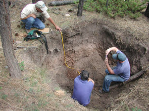 (Click to enlarge) Researchers examine and photograph a cross-section of soil exposed within an excavation pit at the Valles Caldera National