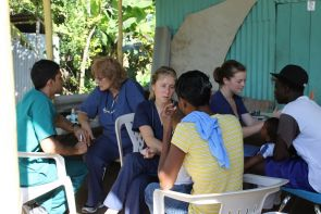 From right to left, first-year medical student Ali Raza, attending physician Dr. Grace Caputo and second-year medical students Brenna Derksen and Chelsea Thomsen see patients in a makeshift clinic in the Dominican Republic during the recent holiday break.