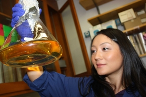 Graduate student and study lead author Eun-Hae Kim checks on a flask containing bacteria growing in a liquid medium. (Photo by Beatriz Verdugo/UANews)