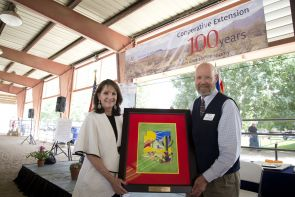 Nationally acclaimed local Tucson artist Diana Madaras honored Arizona Cooperative Extension with a commemorative centennial painting, presented here with UA College of Agriculture and Life Sciences Associate Dean Jeffrey Silvertooth. (Photo: Lynn Ketchum)