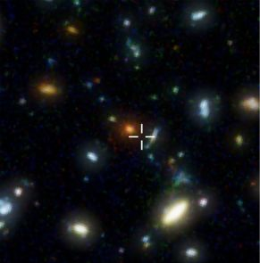 The region of the Hubble Deep Field where HDF850.1 is located (cross) is a glimpse into the abyss of space and time, 12.5 billion light years away. For observations with ordinary, visible light telescopes such as the Hubble Space Telescope, the galaxy is invisible. (Photo: STScI/NASA, F. Walter (MPIA))