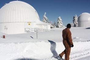 A Mountain Operation technician observes the Catalina Sky Survey telescope and the 32-inch Schulman telescope on Mt. Lemmon. Mountain Operations is the UA team responsible for the maintenance of telescope observatories. During the winter months, the team works to clear away snowfall on and around observatories. (Photo courtesy of Jay Dee Barryman)