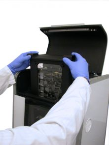 Inserting a loaded disposable cartridge into the Integrated DNA Forensic Analyzer for DNA fingerprinting of a buccal swab sample.