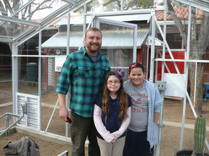 "Manzo Elementary third-grade tour guides Brenda and Kaylee show off the new greenhouse with UA intern Brandon Iker. Brenda and Kaylee are big fans of ""salad parties."""