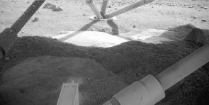 """Phoenix's Robotic Arm Camera took this image on June 2, 2008, on the eighth Martian day of the mission after landing. The light feature in the middle of the image below the leg is informally called """"Holy Cow."""" The dust, shown in the dark foreground, has been blown off of """"Holy Cow"""" by Phoenix's thruster engines. (NASA/JPL-Calech/University of Arizona/Max Planck Institute)"""