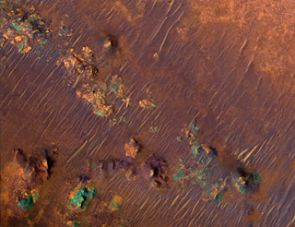 This enhanced-color HiRISE image is part of a much larger HiRISE image of the Nili Fossae region of Mars, recently found to be rich in clay. Clay minerals contain water and may preserve organic materials, important clues about ancient environments that possibly supported life. The purple areas in this false-color image are basaltic, or volcanic, in origin. Orange areas are the clay-rich areas.  The blue-green patches are outcrops of unaltered rocks rich in the mineral pyroxene. HiRISE data has been used to produce a video animation that simulates the high-resolution camera's view as it flew over Nili Fossae.