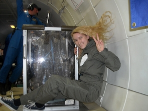 Learning to fly: Shelley Littin salutes from zero-g, next to her team's experimental setup. (Photo by Ernest Bell)
