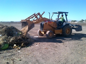 Scott Appleby, UA undergraduate majoring in mechanical engineering and mathematics, powers up a skiploader to move food waste at the San Xavier Co-op Farm. (Photo: Braelyn Jane Smith)