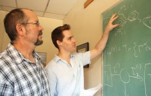 (Click to enlarge) Charles Stafford (left) and Justin Bergfield discuss the flow of electron waves around a benzene ring - the key to the quantum effects allowing for the conversion of heat into electricity.