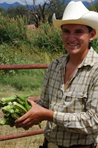 A youth intern at Avalon Organic Gardens, a community-supported agriculture project in Tumacacori, Ariz., carries okra from the garden to a roadside stand. (Photos courtesy Gary Paul Nabhan)