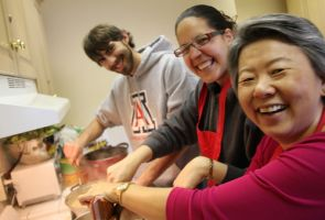 Professor Supapan Seraphin, right, and some of her students have some fun in the kitchen preparing vast quantities of Thai curry for hungry students.