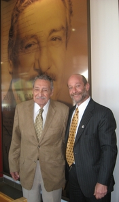 Raul Castro (left) with Rogers College Dean Lawrence Dean Ponoroff in front of Castro's portrait.