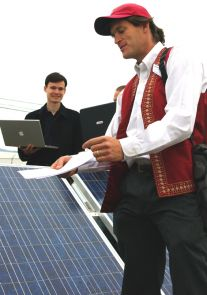Alexander Cronin, right, UA associate professor of physics and optical sciences, monitors daily performance of several different types of photovoltaic modules. Physics doctoral candidate Vincent Lonij, also pictured here, is a member of the monitoring team. (click to enlarge)