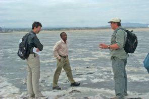 Professor Andrew S. Cohen (left) with HSPDP colleagues Anthony Mbuthia (center) and Doug Schnurrenberger at Lake Magadi, Kenya, a dry soda lake, where one of the drill cores will be collected. (Photo: Craig Feibel)