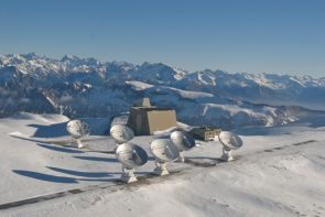 "IRAM's antennas are mounted on rails, combining their signals into the resolving power of a much larger ""virtual antenna."" At maximum separation, they can resolve 0.5 arcseconds of sky at an observing wavelength of 1.3 mm (230 GHz), equal to the apparent size of an apple at a distance of 60 km, or about 37 miles. (Photo: IRAM/Rebus)"
