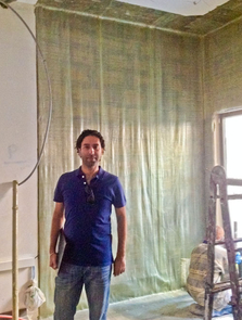 Rabih Hajjar stands in the U.N. building in Beirut as contractors apply blast-resistant fiber-reinforced polymer to the interior wall. (Quakewrap photo)
