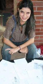 Master's graduate Marisol Badilla displays the O'odham language bingo game drawings students from Sonoyta, Mexico created.