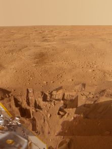 Caption Text: This mosaic of images from the Surface Stereo Imager camera on NASA's Phoenix Mars Lander shows several trenches dug by Phoenix, plus a corner of the spacecraft's deck and the Martian arctic plain stretching to the horizon.  The footpad at the bottom center is about 1 meter (3 feet) below the spacecraft deck seen at the lower left. Overlaid images show trenches dug to either nearly pure water ice or ice-cemented soil. Analyses of samples taken from these trenches give clues to the history of the region.  This approximately true color view combines images taken on several dates during the five months Phoenix studied its surroundings after landing on May 25, 2008.  The Phoenix Mission was led by the University of Arizona, Tucson, on behalf of NASA. Project management of the mission was by NASA's Jet Propulsion Laboratory, Pasadena, Calif. Spacecraft development was by Lockheed Martin Space Systems, Denver. (Credit: NASA/JPL-Caltech/University of Arizona/Texas A&M University)