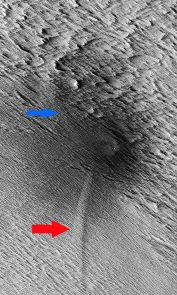 (Click image to enlarge) HiRISE image of the study area showing the central crater with two dagger-like features extending at an angle (red and blue arrows). Called scimitars, these features most likely resulted from shockwave interference just before impact. (Image: NASA/JPL-Caltech/The University of Arizona)