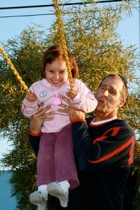 Rick DeMont, associate head coach of the men's swimming and diving team, pushes a little girl on the swings at the Grace Home.