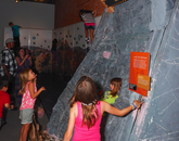 Students play on a climbing wall.