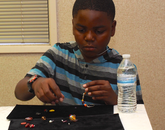 A camper creates beaded jewelry.