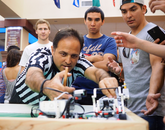 Ricardo Valerdi (center), an associate professor of systems and industrial engineering, separates two unruly robots.