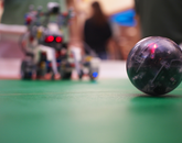The color sensor onboard each robot recognizes the red LEDs on the ball so that they can seek out their target.
