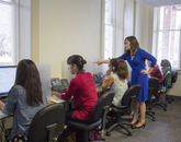 """Sept. 9, 12:02 p.m.: Courtney Robinson (standing), is an office specialist hired in February. Robinson works with current students to answer calls and emails from prospective students and members of the community. About Old Main, she says: """"I really like it. Very different and very pleased."""""""