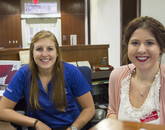 """Sept. 9, 11:56 a.m.: Riley Sullivan (left), a senior studying mathematics, says she previously worked at Bear Down Gym and now prefers Old Main. """"It's a beautiful place,"""" says Sullivan, who works in the Office of Admissions. Erin Przybylinski, a student in the James E. Rogers College of Law, is a student recruiter."""