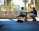 "Sept. 11, 11:30 a.m.: UA alumnus Rich Redel joins Paul Lindvall, a freshman studying engineering, in the shade on the ground floor of Old Main. ""It's a good place for meeting friends to talk with,"" Lindvall says."