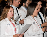First-year med students Savanah McMahon (left) and Sophie Loeb recite the oath during the White Coat ceremony.