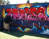 Artist Erode (Onk Akimel O'odham), who goes by Dig Dug, paints live. (Photo: Lexi Obara)