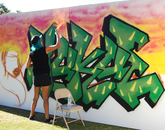 Yuku mists her piece with orange paint, filling in the background. (Photo: Lexi Obara)