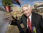 Guy Reed, dean of the College of Medicine – Phoenix, signs the steel beam. (Kris Hanning/UAHS BioCommunications)