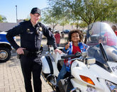 A future Wildcat tries out the ride on a UA Police Department motorcycle.