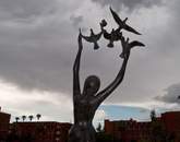 """David Wynne's bronze sculpture, """"Girl With Doves,"""" is near the entrance to the Main Library. (Photo: Patrick McArdle/UANews)"""